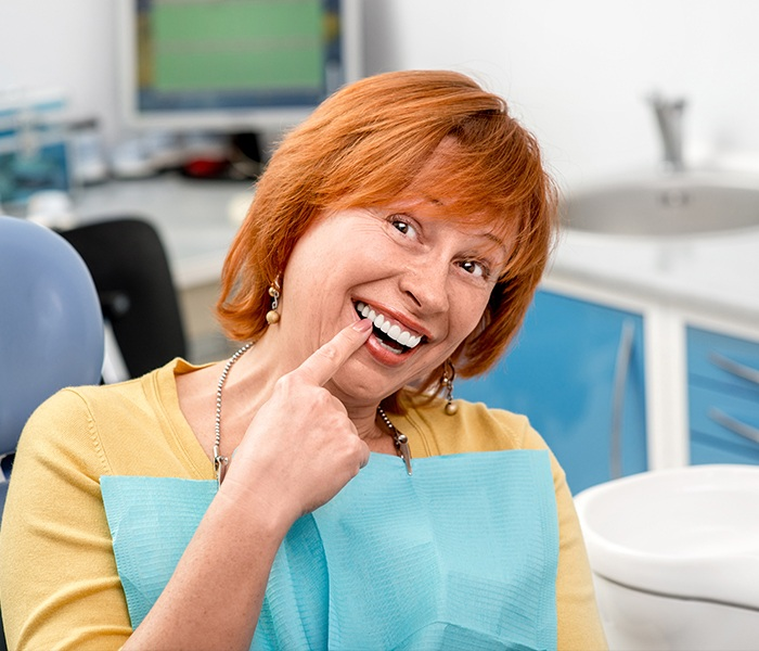 Woman pointing to healthy smile during periodontal maintenance visit