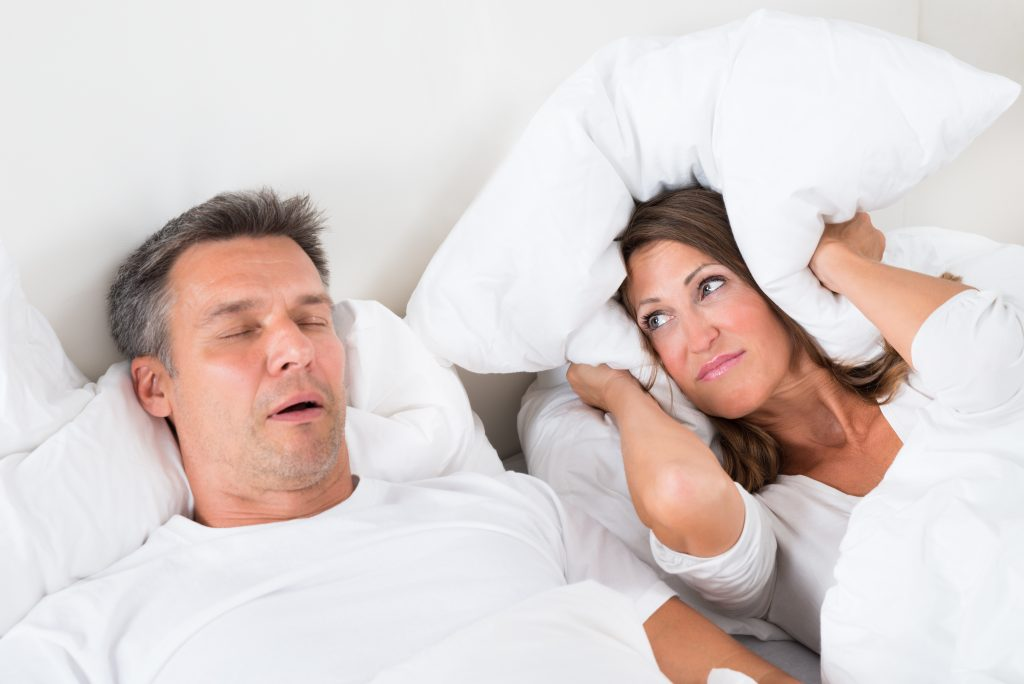 man snoring while partner covers ears