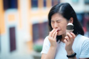 Woman with sensitive teeth and ice cream should visit Rowley dentist