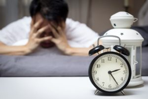 Stressed man covering face in bed; alarm clock